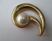 Curved shell shaped gold pin with large pearl