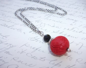 Red cinnabar necklace with black crystal bead