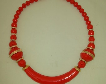 SALE / Red plastic necklace with gold color rings between the red beads 1980s.