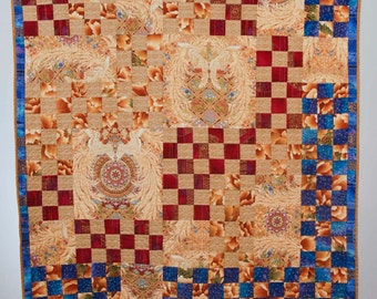 Wings. A 9-patch art quilt wall hanging featuring a stunning lush Classical-motif prints in golds, reds, royal blues.