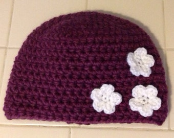 Crocheted hat with flower embellishment.
