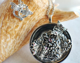 Music box locket, round locket with music box inside, in silver with silver flower filigree and butterfly adornments
