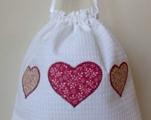 White cotton drawstring bag with pink applique hearts