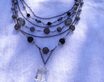 Multi strand gray and black beaded necklace with plain chain strand and a clear acrylic pendant