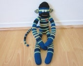 Blue, green, and yellow striped sock monkey plush doll with red heart