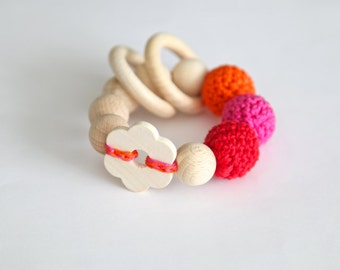 Big flower toy. Teething wooden rattle with pink, red and orange crochet wooden beads and 2 wooden rings.