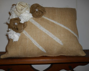 Burlap pillow trimmed in contrasting off white chiffon flowers and darker burlap flowers with lace and pearl trim