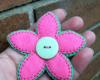 Pink felt flower brooch with green button