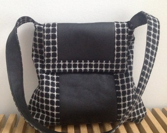 Black and white checkered messenger bag sewn from wool tweed and leather