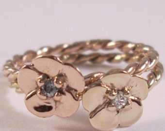 Two tone 14 karat rose and yellow  gold flowers with diamond accents