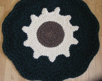 This is a round braided rug which is scalloped.  It has a pale yellow sunflower in the center with a dark green background.