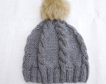 Gray hand knitted cabled hat with fur camel pom pom