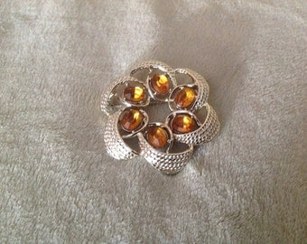 A Gold Tone Brooch has 6 Yellow Gold sparkling stones.