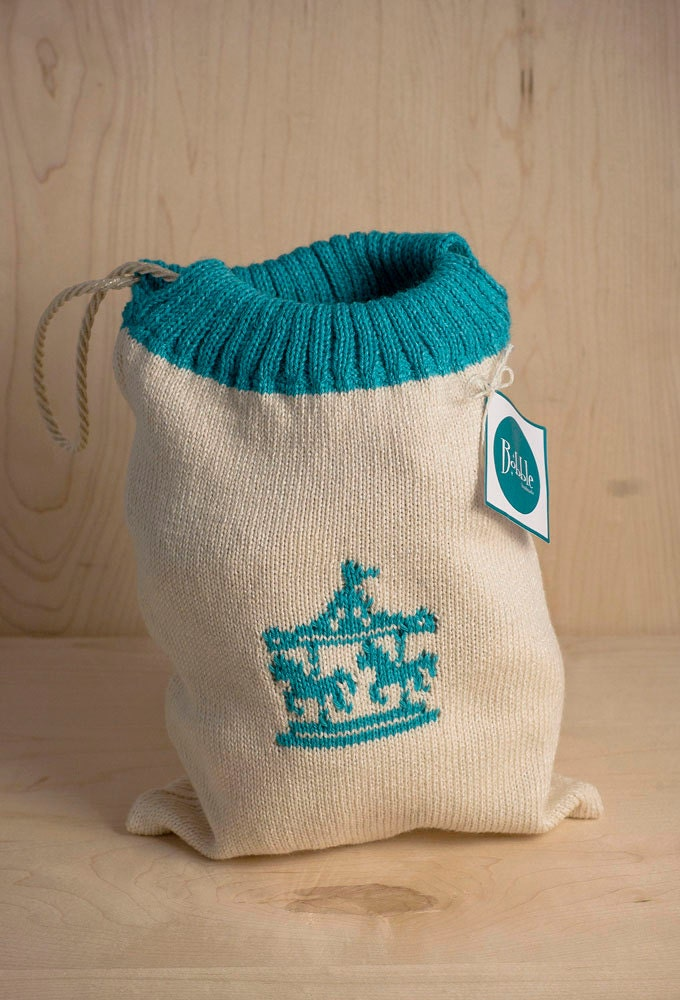 Mini knitted drawstring bag with carousel motif by Bobblehandmade