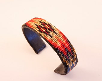 Geometric Design Beaded Cuff Bracelet in Reds and Golds on a Black Background. This Piece will Dress Up any Outfit, is Handmade by Artist