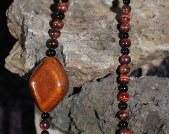 Brown and black necklace with large brown procelain bead.