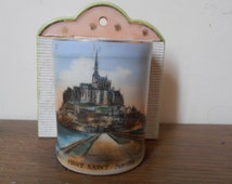 A souvenir porcelain match container with a scene of the Mont St Michel Abbey