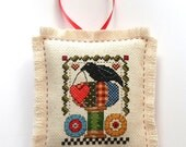 Completed Cross Stitch Crow and Spool Mini Pillow Ornament
