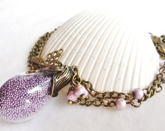 Teardrop glass orb necklace filled with delicate purple fiber beads and bronze accents
