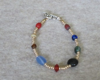 Gold colored bracelet with mixed glass beads