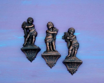 Set of three 1969 Dionysian harvest mythical children ornate filigree kitschy opulance faux aged metal boho sculptural wall reliefs