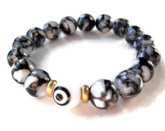 Evil eye bracelet, black and white stretch bracelet, wrist mala with evil eye bead, brass beads, and mother of pearl shell composite beads