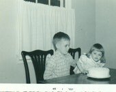 Happy Second Birthday Little Girl Blowing Out Candles on Cake With Brother 1964 Vintage Black White Photo Photograph