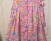 Butterfly dress size six. Pink background with multicolored butterflies and sparkles