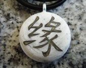 KARMA Japanese kanji symbol hand carved on a polymer clay grey granite color background.  Pendant comes with a FREE 3mm necklace