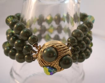 Triple strand green bead bracelet with gold tone clasp.