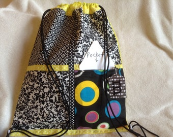 Yellow against black and white on a yellow ripstop nylon drawstring backpack with front zipper pocket
