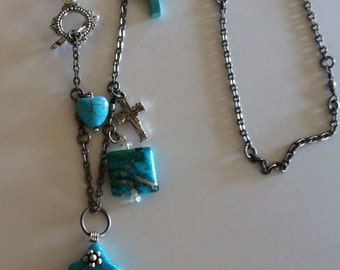 """Three inch turquoise cross on a 24"""" antiqued silver chain with turquoise and silver charmers."""