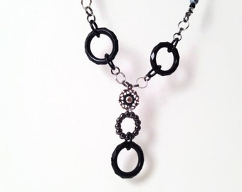 Black circular necklace with silver accents
