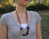 Women's rosette statement necklace on a gray ribbon with bright variegated fabric that can be adjusted to wear short or long
