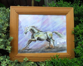 Pastel drawing of a running unicorn in a wooden frame