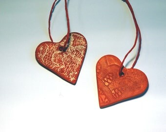 Set of two red medium ceramic Valentines day hearts ornaments with lace pattern.