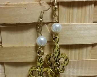 Gold tone hammered fleur de lis dangle earrings with white glass pearl.