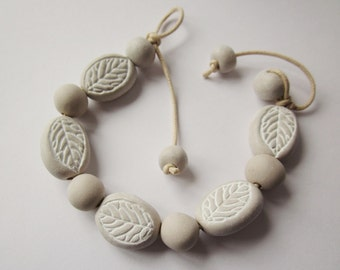 Bracelet with incised leaf design in natural and white