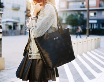 Black Tote bag with integrated light inside. Made of recycled seatbelt. 8 pockets.