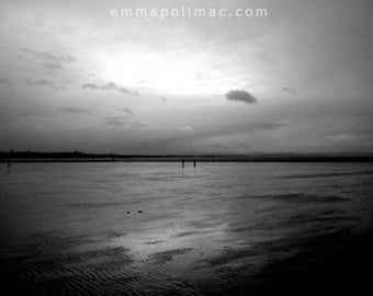 Black and white beach photography: seascape with figures, overcast sky, grey, dark wet sand, moody. Ready-to-frame zen art.