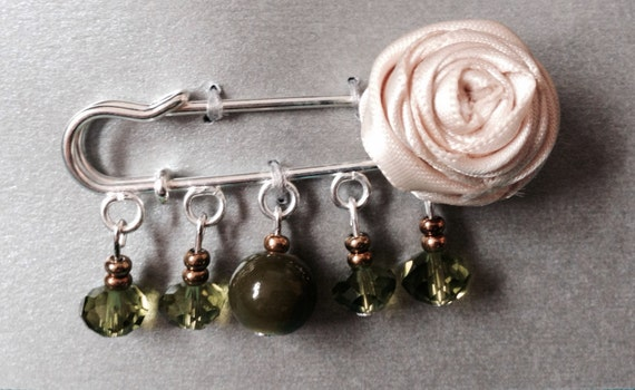 Ivory rose kilt pin, with green and bronze coloured beads