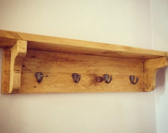 Rustic wooden coat hook rack with shelf.