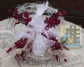Holder wedding rings with feathers and red flowers