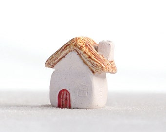 Miniature ceramic house with thatched roof and red door