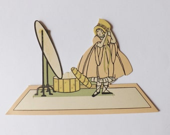 Vintage place card little girl dressing up in front of mirror with pink dress and yellow bonnet