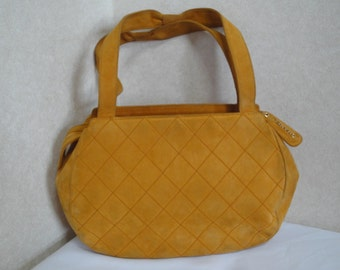 Vintage CHANEL yellow orange genuine suede leather stitch design round tote bag with gold tone logo charm pull.