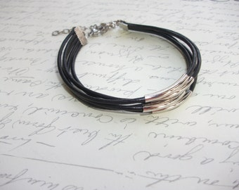 Multi strand black leather bracelet with silver tubes
