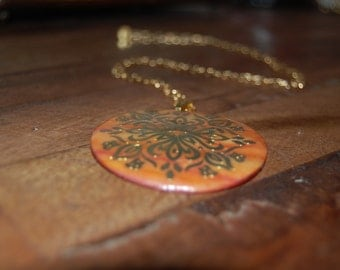 "Pendant necklace with 14"" gold chain, 2"" round shell-like pendant in shades of orange/peach with gold design"