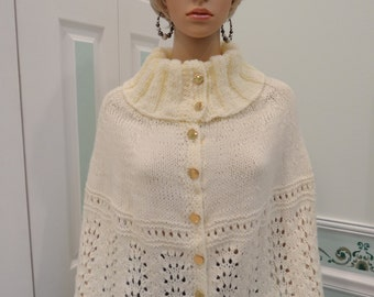 LADIES KNITTED CAPE: Ivory/ Creme,   cape, turtle neck, hand knitted, in soft ivory/cream, worsted weight yarn, with 12 gold buttons