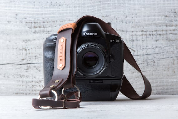 Personalized leather camera strap belt in brown color with tan leather tags.